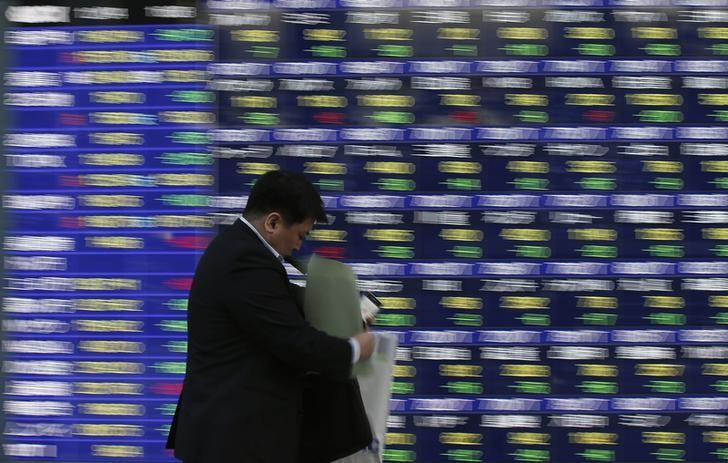A man walks past a stock quotation board outside a brokerage in Tokyo December 4, 2013. REUTERS/Toru Hanai/Files