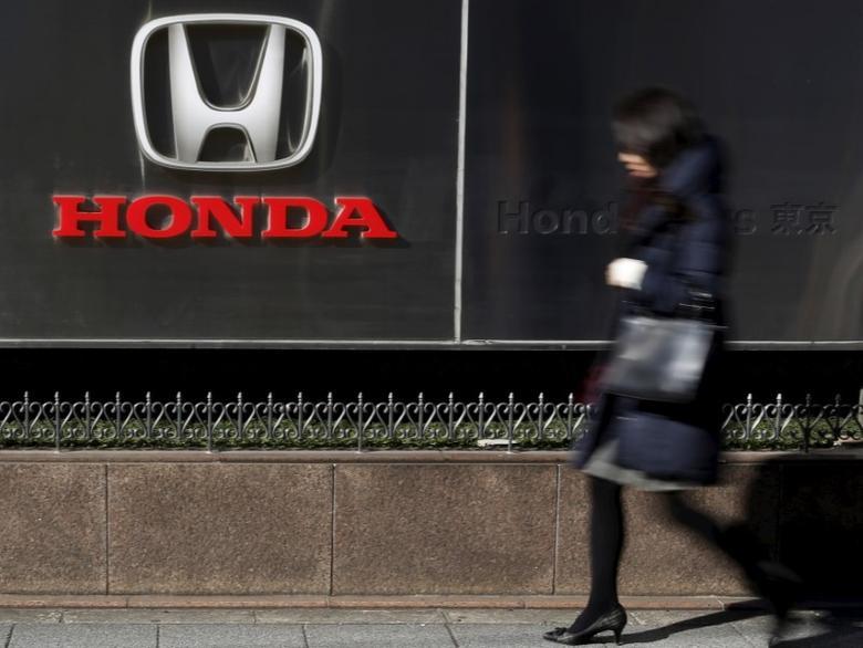 A woman walks past a logo of Honda Motor Co outside the company's dealership in Tokyo, Japan, January 27, 2016. REUTERS/Yuya Shino