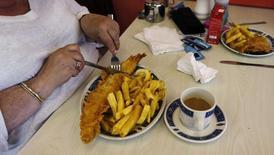"""Una mujer come pescado y papas fritas en un restaurant Jack's Fish & Chips, en Londres. 18 de mayo de 2012. El sector de servicios de Gran Bretaña creció más sólidamente a lo previsto en septiembre, mostró un sondeo el miércoles, lo que aumentó las dudas sobre la necesidad de un nuevo recorte de tasas de interés por parte del Banco de Inglaterra en noviembre para amortiguar el impacto por el """"Brexit"""". REUTERS/Eddie Keogh"""