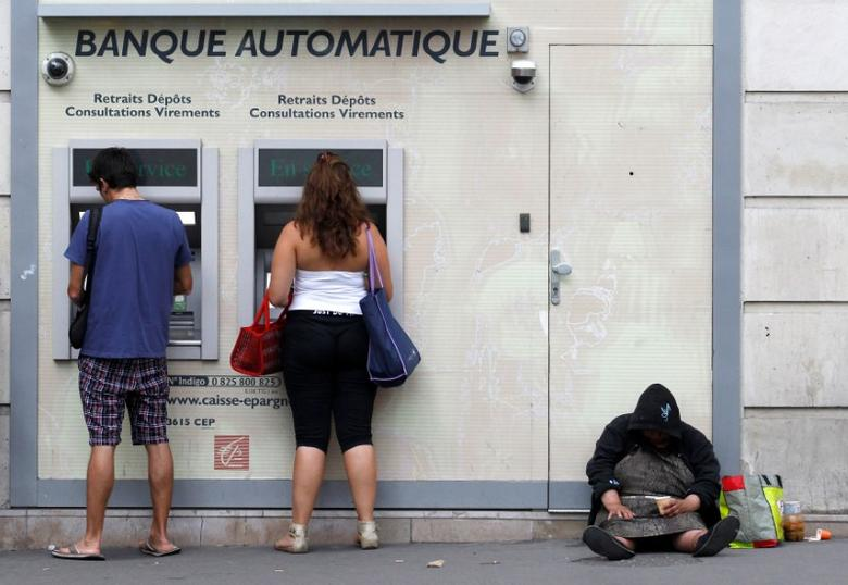 An homeless woman sits on a footpath while people withdraw money from ATMs along a main road in central Paris August  22, 2011.  REUTERS/Yves Herman/File Photo