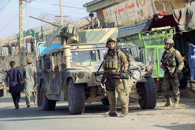 Afghan security forces keep watch in front of their armoured vehicle in Kunduz city, Afghanistan October 4, 2016. REUTERS/Nasir Wakif