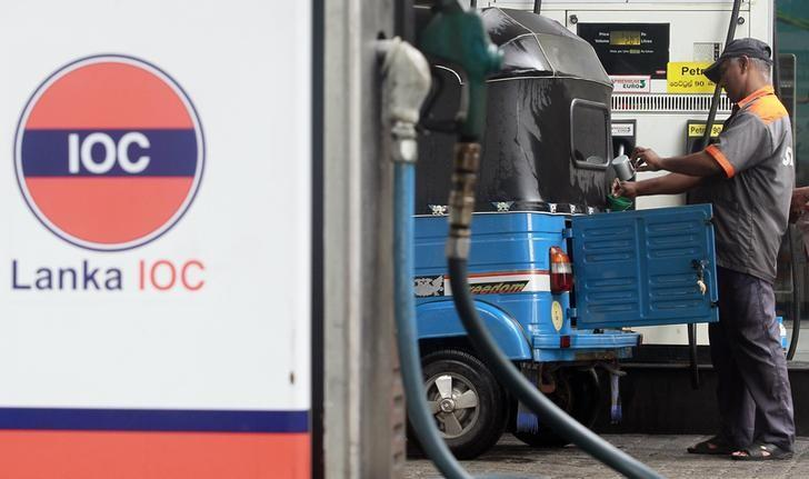 A worker fills the tank of a motorised vehicle, known locally as a ''three-wheeler'', at a Lanka India Oil fuel station in Colombo April 25, 2012.  REUTERS/Dinuka Liyanawatte/Files