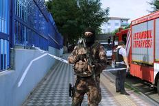 Полицейский стоит рядом с местом взрыва в Стамбуле. Как минимум пять человек получили ранения, один из них - тяжелые, в результате срабатывания взрывного устройства, прикрепленного к мотоциклу, возле полицейского участка на юго-западе Стамбула в четверг, сообщили местные чиновники.  REUTERS/Huseyin Aldemir