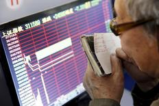 Инвестор в Шанхае смотрит на экран с информацией о торгах. Фондовые индексы Гонконга снизились по итогам торгов пятницы под давлением акций компаний потребительского и энергетического секторов, в то время как инвесторы фиксировали прибыль в преддверии длинных выходных и перед публикацией важной трудовой статистики США, которая может повлиять на решение ФРС о сроках повышения процентных ставок.  REUTERS/China Daily