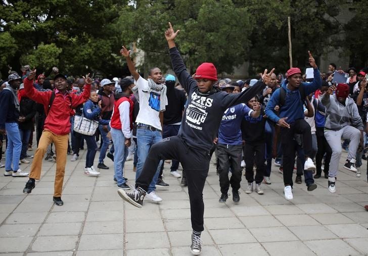 Students chant slogans during clashes with the South African police protect at Johannesburg's University of the Witwatersrand, South Africa, October 4, 2016. REUTERS/Siphiwe Sibeko