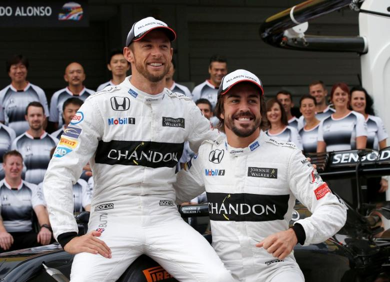 Formula One - Japanese Grand Prix - Suzuka Circuit, Japan- 7/10/16. McLaren's drivers Jenson Button of Britain and Fernando Alonso of Spain attend the team photo session before first practice.  REUTERS/Toru Hanai