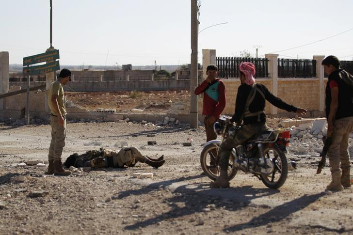 Rebel fighters stand near a dead body, which according to them, belongs to an Islamic State militant, in Turkman Bareh village, after rebel fighters advanced in the area, in northern Aleppo Governorate, Syria, October 7, 2016. REUTERS/Khalil Ashawi