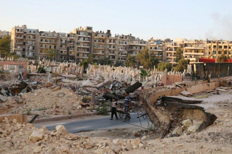 People walk near an over-crowded graveyard in the rebel held al-Shaar neighbourhood of Aleppo, Syria October 6, 2016. REUTERS/Abdalrhman Ismail