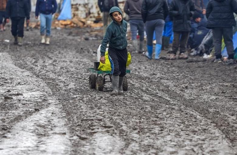A young migrant pulls a trolley in a muddy field at a camp of makeshift shelters for migrants and asylum-seekers from Iraq, Kurdistan, Iran and Syria, called the Grande Synthe jungle, near Calais, France, February 3, 2016. REUTERS/Yves Herman/File Photo