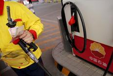 Un empleado sostiene un surtidor de combustible en una gasolinera de PetroChina en Pekín. 21 de marzo de 2016. La eficiencia en energía global, o el nivel de producto interno bruto generado a partir de una unidad específica de energía, mejoró en 1,8 por ciento el año pasado, mostró el lunes un reporte la Agencia Internacional de Energía (AIE). REUTERS/Kim Kyung-Hoon/File Photo