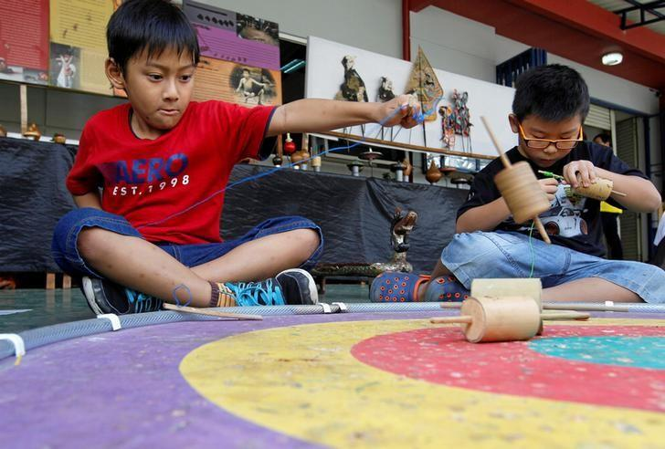 Boys play with spinning tops during an event for traditional games at a school in Jakarta, Indonesia, October 1, 2016. Picture taken October 1, 2016. REUTERS/Iqro Rinaldi