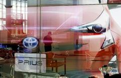A woman is reflected on a screen showing Toyota Motor Corp's Prius hybrid car at the company's showroom in Tokyo, Japan June 14, 2016.    REUTERS/Toru Hanai/File Photo