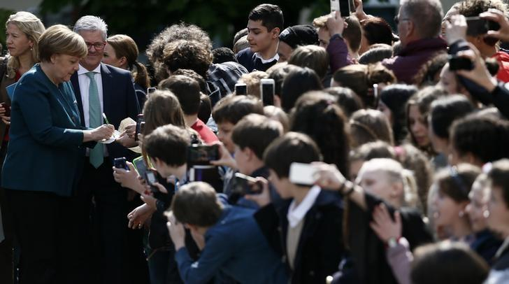 German Chancellor Angela Merkel signs autographs as she visits the French secondary school Lycee Francais in Berlin, Germany, May 3, 2016. REUTERS/Hannibal Hanschke /Files