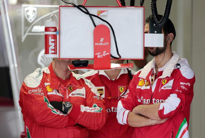 Members of the Ferrari F1 team look at a monitor inside the team garage during the qualifying session for the Formula One Japanese Grand Prix at Suzuka Circuit October 8, 2016. REUTERS/Yuya Shino/Pool