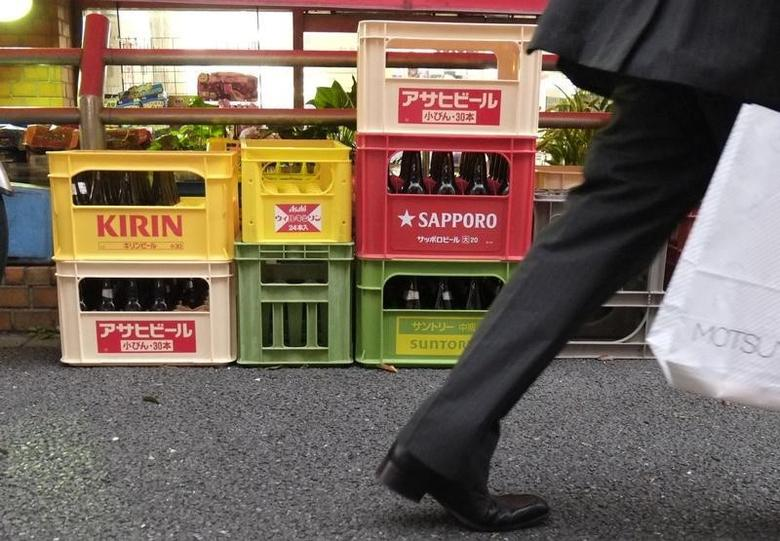 Cases of beer (top L) by Japanese brewer Kirin Holdings and other makers are seen outside a store in Tokyo July 10, 2014.    REUTERS/Toru Hanai