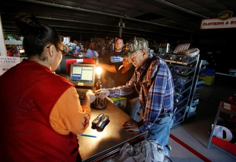 A cashier uses a bare bulb powered by a portable generator in a hardware store operating during a lengthy electricity outage in Elizabethtown. REUTERS/Jonathan Drake
