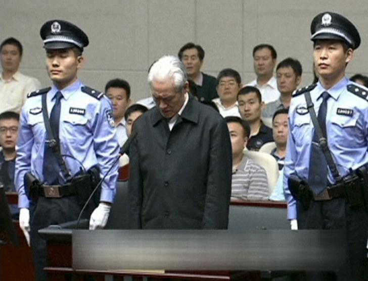 Zhou Yongkang, China's former domestic security chief, stands between his police escorts as he listens to his sentence in a court in Tianjin, China, in this still image taken from video provided by China Central Television and shot on June 11, 2015. REUTERS/China Central Television via REUTERS TV/Files