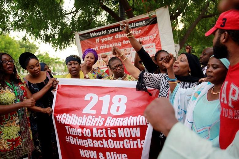 Members of the #BringBackOurGirls (#BBOG) campaign stand behind a banner with Number 218 during a sit-out in Abuja, Nigeria May 18, 2016, after receiving news that a Nigerian teenager kidnapped by Boko Haram from her school in Chibok more than two years ago has been rescued. REUTERS/Afolabi Sotunde