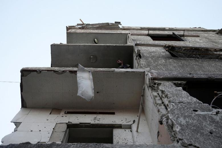 A man stands on the balcony of a damaged building after an airstrike yesterday in the rebel held Douma neighborhood of Damascus. REUTERS/Bassam Khabieh