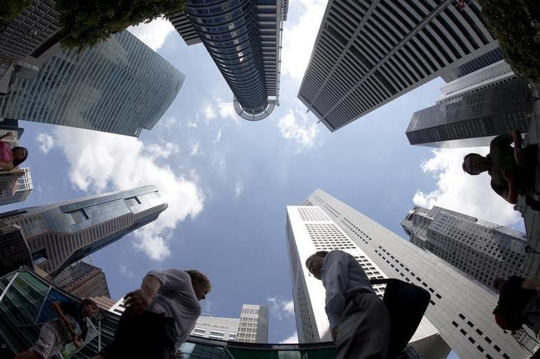 People walk past office buildings at the central business district in Singapore April 14, 2015.  REUTERS/Edgar Su