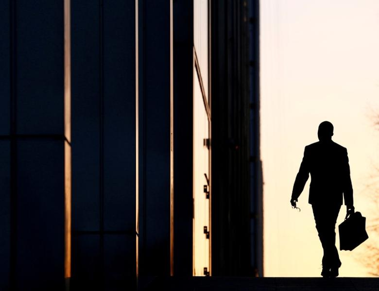 A worker arrives at his office in the Canary Wharf business district in London, Britain, February 26, 2014.   REUTERS/Eddie Keogh/File Photo