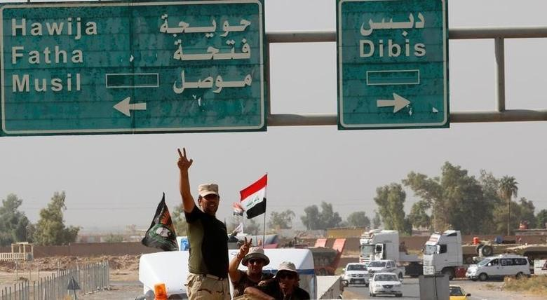 Members of Iraqi security forces gesture as a convoy advances on the outskirts of Mosul, to fight against Islamic State militants, in Kirkuk, Iraq, October 12, 2016. REUTERS/Ako Rasheed