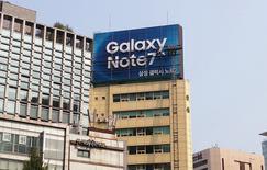 Trabajadores retirando un cartel publicitario del celular Samsung Galaxy Note 7 desde un edificio en Seúl, Corea del Sur. 14 de octubre de 2016. Samsung Electronics Co Ltd dijo el viernes que espera sufrir un impacto en su ganancia operativa de unos 3.000 millones de dólares en los próximos dos trimestres luego de que dejó de producir su teléfono inteligente defectuoso Galaxy Note 7. REUTERS/Staff