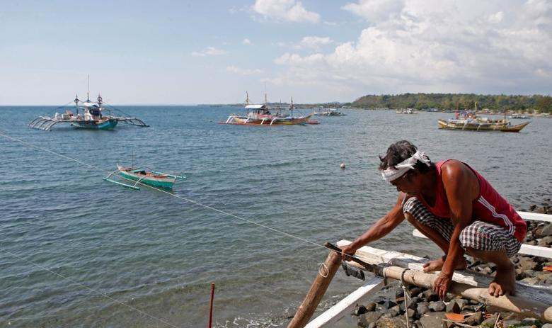 A fisherman repairs his boat overlooking fishing boats that fish in the disputed Scarborough Shoal in the South China Sea, at Masinloc, Zambales, in the Philippines April 22, 2015. REUTERS/Erik De Castro