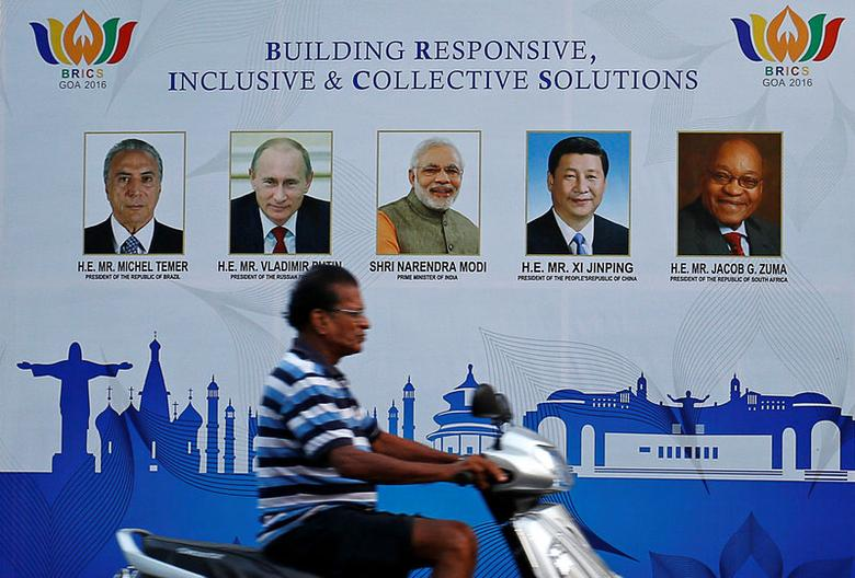 A man rides past a billboard near one of the venues of BRICS (Brazil, Russia, India, China and South Africa) Summit in Benaulim, in the western state of Goa, India October 14, 2016. REUTERS/Danish Siddiqui