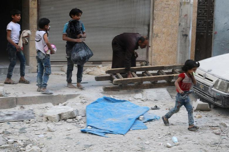 Children react in a damaged site after an airstrike in the besieged rebel-held al-Qaterji neighbourhood of Aleppo, Syria October 14, 2016. REUTERS/Abdalrhman Ismail