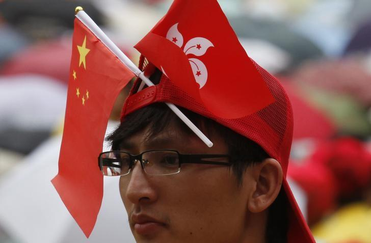 A spectator wears a cap decorated with Chinese and Hong Kong national flags during a gala show attended by thousands at Hong Kong Stadium July 1, 2012 to mark the 15th anniversary of the territory's handover to Chinese sovereignty from British rule. REUTERS/Bobby Yip/File Photo