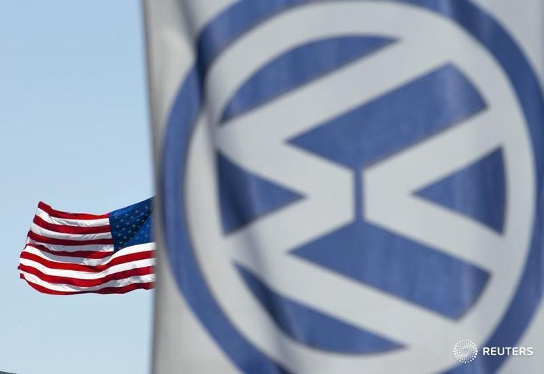 An American flag flies next to a Volkswagen car dealership in San Diego, California September 23, 2015. Volkswagen Chief Executive Martin Winterkorn resigned on Wednesday, succumbing to pressure for change at the German carmaker, which is reeling from the admission that it deceived U.S. regulators about how much its diesel cars pollute.  REUTERS/Mike Blake  - RTX1S50X