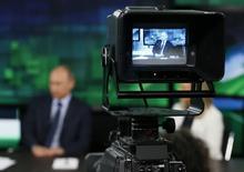 Президент России Владимир Путин в видоискателе телекамеры в студии телеканала Russia Today (RT) в Москве 11 июня 2013 года. Финансируемый за счет налогоплательщиков российский телеканал пожаловался в понедельник, что британский банк NatWest без объяснений отказал в обслуживании. REUTERS/Yuri Kochetkov/Pool