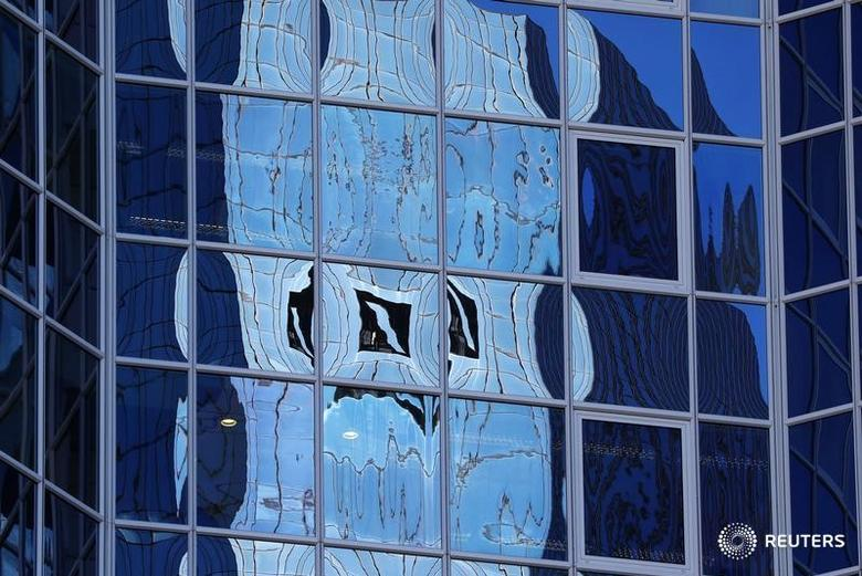 The logo of Germany's Deutsche Bank is reflected in the windows of a skyscraper in Frankfurt, Germany, October 5, 2016.   REUTERS/Kai Pfaffenbach  - RTSQURL