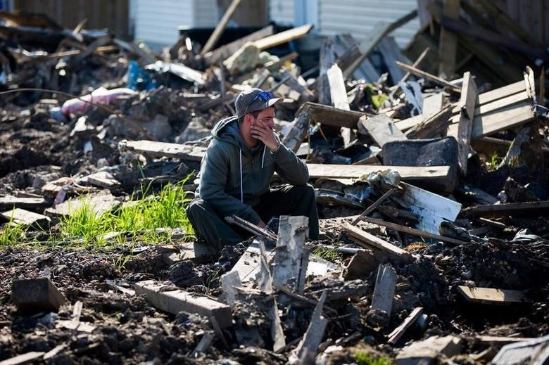 A resident looks over the damage in the Timberlea neighbourhood as thousands of evacuees who fled a massive wildfire begin to trickle back to their homes in Fort McMurray, Alberta, on Canada June 2, 2016. REUTERS/Topher Seguin/File Photo