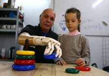 Sergey Galtsev builds a children's pyramid with his granddaughter Anna while testing a prosthetic right hand, made by his son Oleg, in Minsk, Belarus October 16, 2016. REUTERS/Vasily Fedosenko