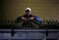 Un trabajador carga botellas de vino en una planta cerca de Cape Town. 29 de noviembre de 2012. La producción mundial de vinos caería este año a su menor nivel desde 2012, principalmente por condiciones climáticas adversas que afectaron los rendimientos en Francia y Sudamérica, según estimaciones publicadas el jueves por el organismo sectorial OIV. REUTERS/Mike Hutchings/File Photo