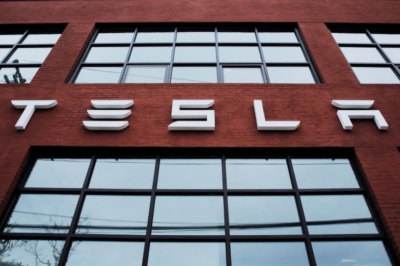 A Tesla logo hangs on a building outside of a Tesla dealership in New York, U.S., April 29, 2016. REUTERS/Lucas Jackson/File Photo