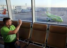 Мужчина фотографирует самолет в аэропорту Домодедово. 6 ноября 2015 года. Авиакомпании российской Группы S7 увеличили перевозки пассажиров на 27,3 процента в сентябре 2016 года, сообщила компания в понедельник. REUTERS/Maxim Zmeyev
