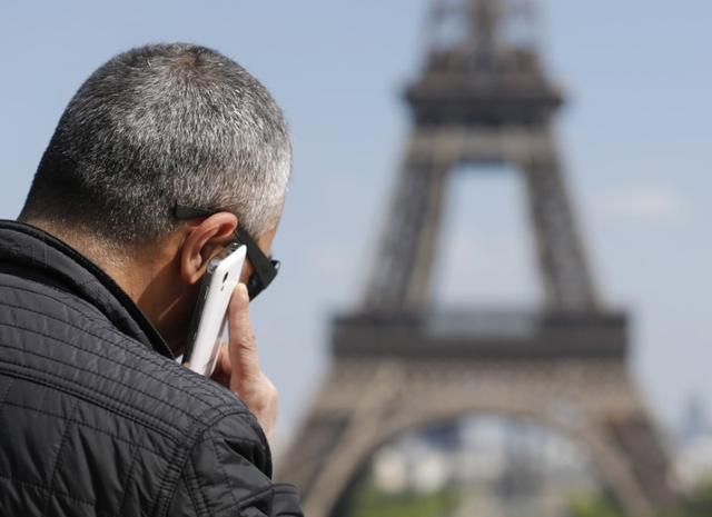 A man makes a phone call using his mobile phone at the Trocadero Square near the Eiffel Tower in Paris, May 16, 2014. REUTERS/Christian Hartmann