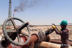 Рабочий проверяет вентиль нефтепровода на НПЗ Аль-Шейба в Басре, Ирак. Цены на нефть продолжили снижаться в понедельник, после того как не входящие в ОПЕК страны на консультациях в субботу воздержались от конкретных обязательств ограничения добычи нефти ради подъема цены, дав понять, что прежде ждут преодоления разногласий внутри картеля. REUTERS/Essam Al-Sudani/File Photo