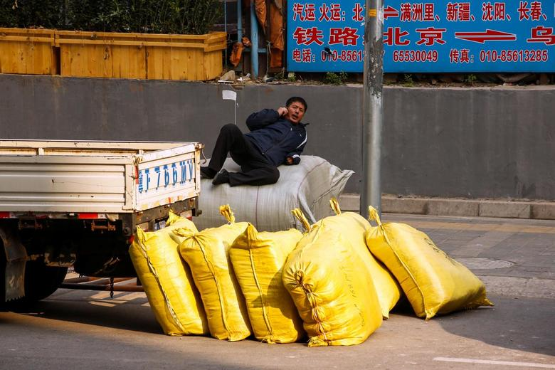 A worker sits on top of sacks with construction material, outside a construction site in Beijing, China