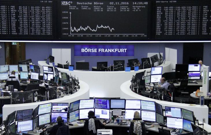 Traders work at their desks in front of the German share price index, DAX board, at the stock exchange in Frankfurt, Germany, November 2, 2016.