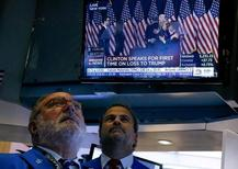 Traders watch, as Hillary Clinton addresses her staff and supporters about the results of the U.S. election, on the floor of the New York Stock Exchange (NYSE) the morning after the U.S. presidential election in New York City, U.S., November 9, 2016. REUTERS/Brendan McDermid