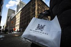 A woman holds a Hudson's Bay shopping bag in front of the Hudson's Bay Company (HBC) flagship department store in Toronto January 27, 2014.    REUTERS/Mark Blinch