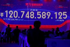 People watch a screen displaying the total value of goods sold during Alibaba Group's 11.11 Singles' Day global shopping festival in Shenzhen, China, November 12, 2016. REUTERS/Bobby Yip