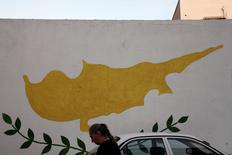 A woman walks in front of Cypriot flag painted on a wall in capital Nicosia, Cyprus November 11, 2016. REUTERS/Yiannis Kourtoglou