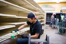 FILE PHOTO - A crew member cleans the inside of the Family Foods grocery store after clearing all the expired food off the shelves as thousands of evacuees who fled a massive wildfire begin to trickle back to their homes in Fort McMurray, Alberta, Canada on June 2, 2016. REUTERS/Topher Seguin/File Photo