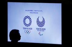 A woman is silhouetted against a monitor showing Tokyo 2020 Olympics and Paralympics emblems during the Olympic and Paralympic flag-raising ceremony at Tokyo Metropolitan Government Building in Tokyo, Japan, September 21, 2016.  REUTERS/Toru Hanai