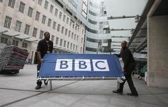 Рабочие размещают баннер рядом с главным входом в штаб-квратиру Би-би-си в Лондоне. Британская вещательная корпорация Би-би-си объявила в среду, что начнет транслировать свои передачи на 11 новых языках и откроет вещание в Северной Корее, а также увеличит объем контента для русскоязычных пользователей.   REUTERS/Peter Nicholls/File Photo